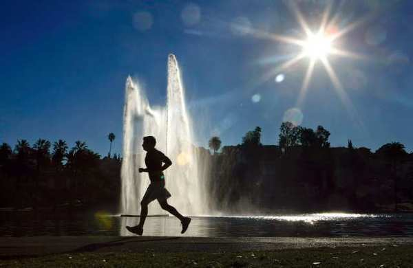 A jogger is silhouetted against a water fountain backdrop at Echo Park Lake in Los Angeles. Summer productivity, already low, will take another hit this holiday week.