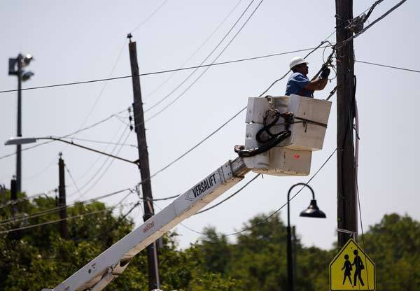 An electrician works on restoring power to a neighborhood in Hyattsville, Md. Relentless heat was forecast for much of the eastern U.S. for a fourth straight day on Monday, after violent storms killed at least 15 people and knocked out power to more than 3 million customers.