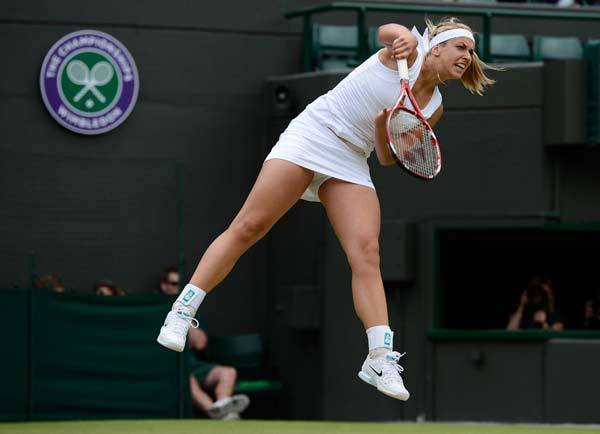 Sabine Lisicki of Germany serves to Maria Sharapovaof Russia during their women's singles tennis match at the Wimbledon tennis championships in London.