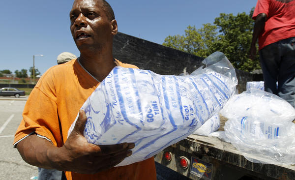 Baltimore city worker Joe Lane give away bags of ice at the Northwood Plaza shopping center.