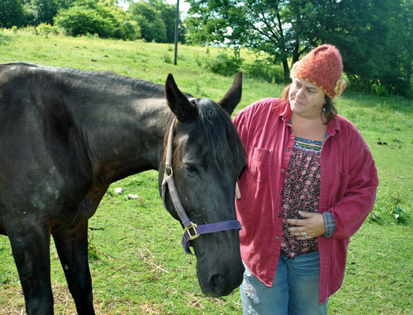 Nicole Shaw stands beside one of 10 rescued horses on a farm near Hollsopple