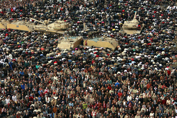 Members of the Egyptian army pray with protesters in Cairo's Tahrir Square on Feb. 11, 2011, the day that President Hosni Mubarak bowed to popular pressure and agreed to step down. In 2011, youth-driven uprisings toppled autocratic regimes in Tunisia, Egypt and Libya.