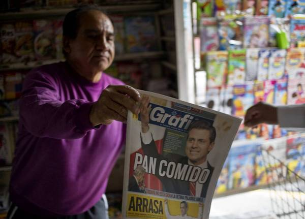 A vendor displays a newspaper featuring the Institutional Revolutionary Party's Enrique Peña Nieto, the winner of Mexico's presidential election.