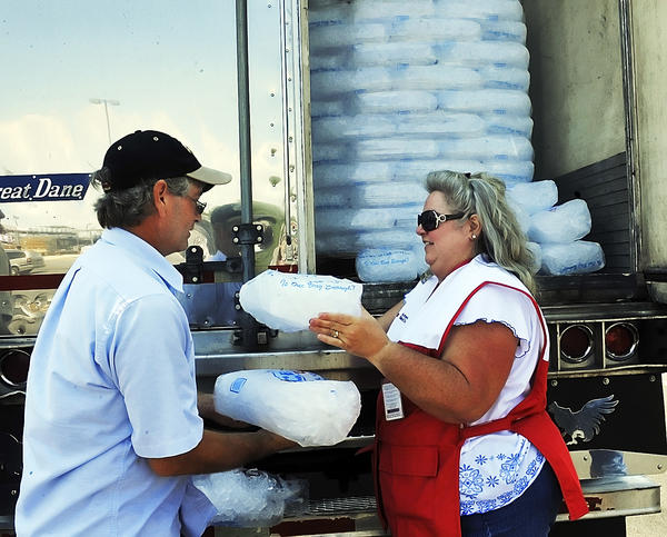 Tom Marchese gets bags of ice from Jennifer Carpenter of the American Red Cross in the parking lot of Lowes in Martnsburg,W.Va., on Monday. People without power were given water and ice.