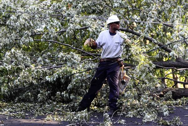 ComEd lineman LaVelle Short clears a garage roof near a downed tree and power lines Monday in Westchester.