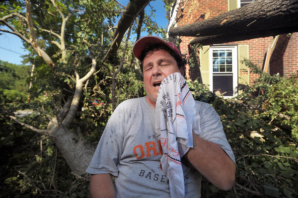 Tony Sartori shows how he has been trying to keep cool since the storm of Friday night knocked out the power all along Gittings Ave, and knocked down a large tree on his house. He said his mother would always take a wet cloth in the summer, when he was growing up in Baltimore, and cool him off, either by putting it on his neck or washing his face with it; which he now does several time a day. Tony said the water is just too cold for him to take a shower.