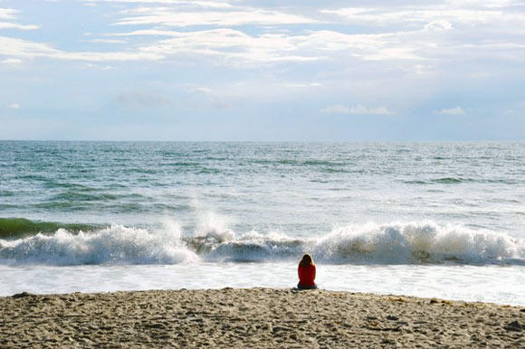 An early morning beach goer looks out over the Atlantic Ocean