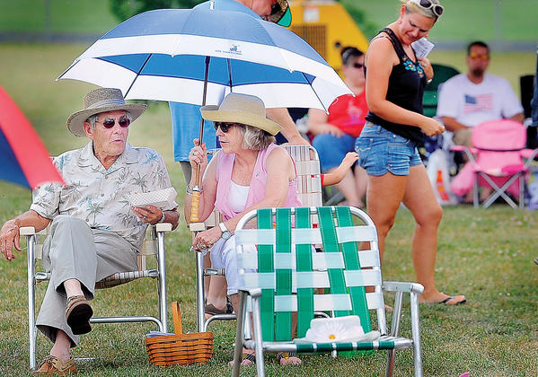 Don and Jane Kriner of Clear Spring enjoy the music of Take Two while sitting under their umbrella during the annual Clear Spring Independence Jam on the grounds of Plumb Grove Mansion.