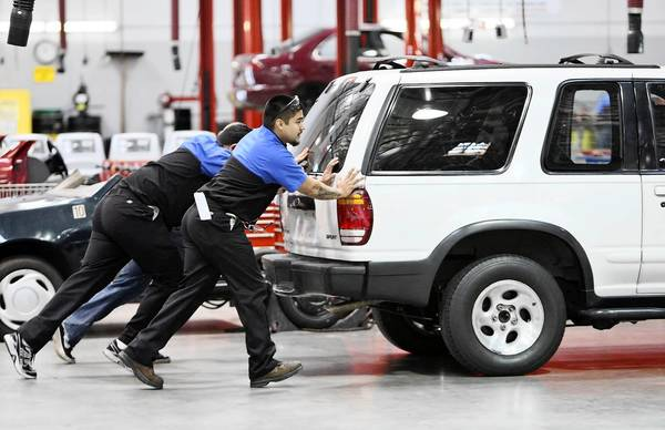 Automotive technology students push a vehicle onto a lift at WyoTech Long Beach, one of several campuses of the for-profit school.