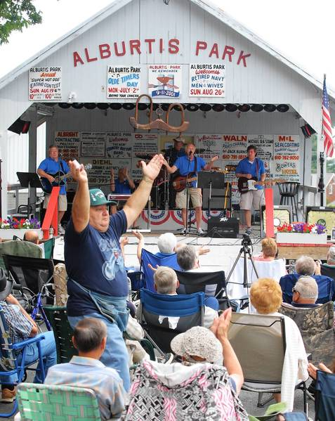 "Concert-goers enjoy ""Crazy Elmer"" (Clenroy Geist of Alburtis) and ""The Outlaws"" at a recent performance in Alburtis Community Park."
