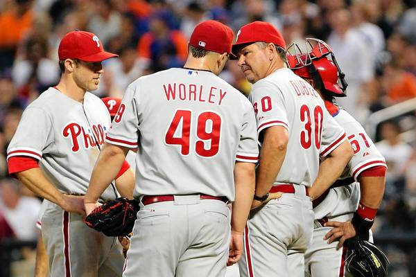 Philadelphia Phillies pitching coach Rich Dubee (30) visits starting pitcher Vance Worley (49) during the fourth inning against the New York Mets at Citi Field.