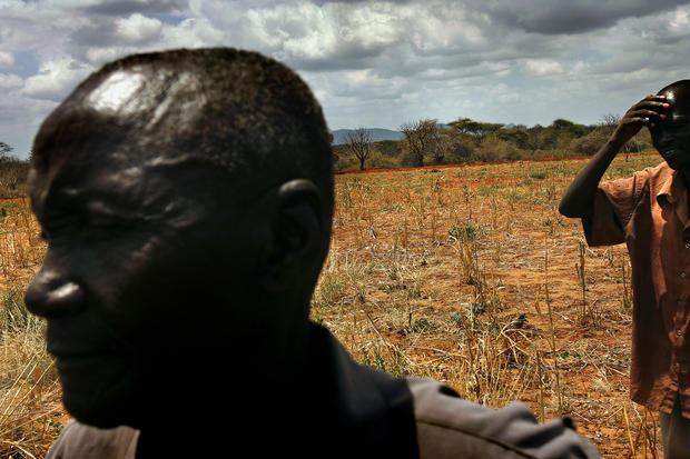 James Mukunga, left, has dealt with years of drought-ruined crops on the small farm he shares with his wife and 12 children in eastern Kenya, about 200 miles from the refugee camps. The family chopped down their few remaining trees to make charcoal to sell. (Rick Loomis / Los Angeles Times)