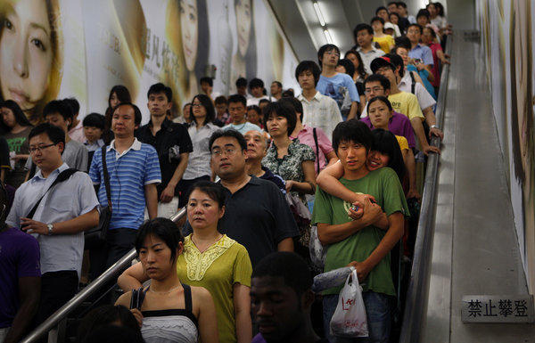 An escalator in the Beijing subway is jammed with people. China's situation powerfully illustrates how rising consumption and even modest rates of population growth magnify each other's impact on the planet. (Rick Loomis / Los Angeles Times)