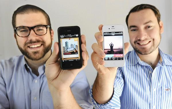 Josh Spears, left, and Dan Sines, both CEOs of Woofound,show their mobile app.