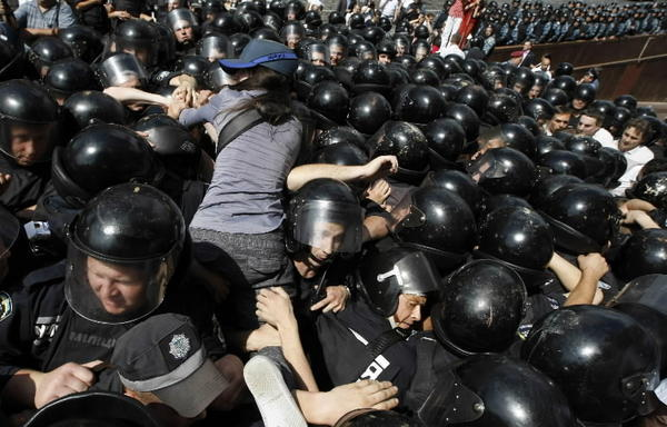 An opposition supporter climbs over the heads of riot police during a rally to protest against a Russian language bill passed by parliament in Kiev July 4, 2012. Hundreds of protesters clashed with riot police in central Kiev and Ukraine's parliament speaker offered to resign on Wednesday amid uproar after a move to boost the status of the Russian language in the former Soviet Republic. Riot police fired tear gas and used batons to push back protesters, who had massed in front of a building where President Viktor Yanukovich was due to hold a news briefing. The bill would upgrade the status of Russian in the former Soviet republic.