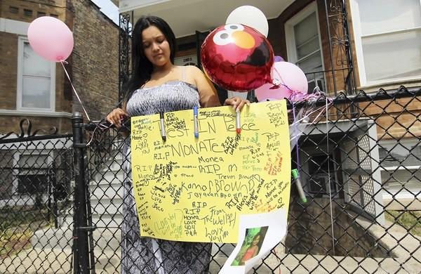 Sophia Lucio stands Tuesday near a memorial for her 5-year-old daughter Monet Robinson at her home on South Millard Avenue. The girl was struck and killed by a hit-and-run driver on Monday evening.