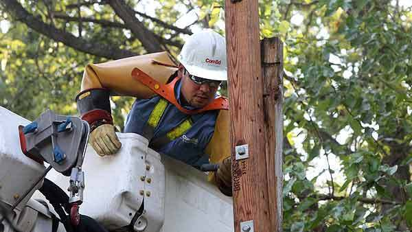 ComEd lineman Alex Alvarez secures the primary arm on a utility pole while working in Westchester Monday.