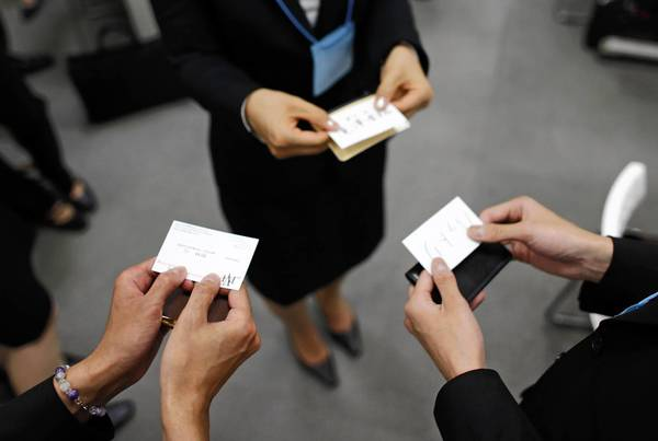 Japanese job-hunting students on the hunt for employmentdressed in suits practice swapping business cards during a business manners seminar at a placement center in Tokyo in May.