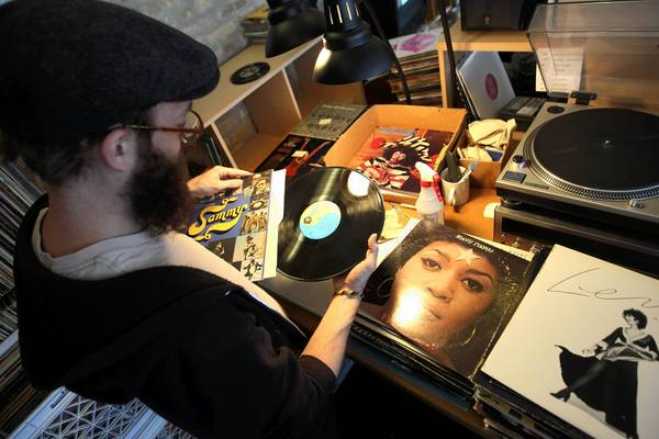 Dusty Groove employee Bryan Lear sorts through stacks of records that store owner Rick Wojcik bought from WGN radio. The records were in storage at the radio station.