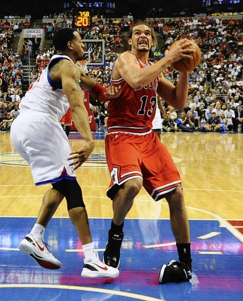 Joakim Noah rolls his ankle while driving to the basket against the 76ers' Andre Iguodala in Game 3.
