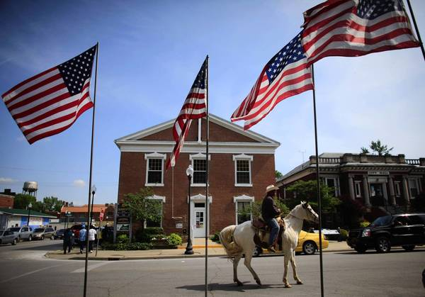 A cowboy rides a horse through town May 6 as he watches a Cinco de Mayo celebration in Beardstown, Ill. Thousands gathered for the event, which is emblematic of the cultural diversity in the farm town. A local meatpacking plant has proved to be a big draw for immigrants