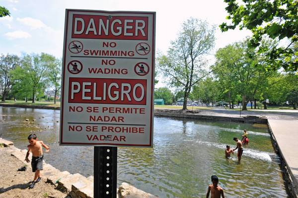 People wade and swim in Jordan Creek near signs posted by the city of Allentown warning them not to do so.