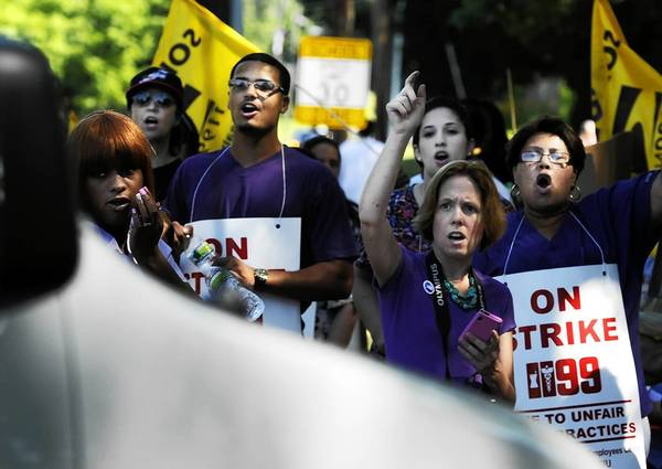 Striking health care workers shout at replacement workers entering the Newington Health Care Center in Newington Tuesday morning.