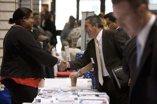 A job seeker shakes hands with an employer at the Veterans On Wall Street job fair last month in New York. Planned layoffs announced in June were at their lowest level in more than a year, according to a consultant's report.