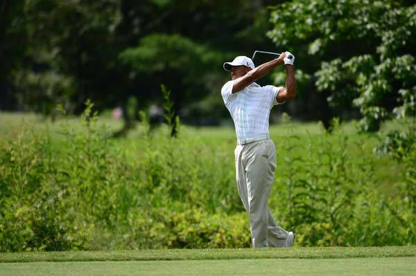 Tiger Woods hits from the rough on the 17th fairway during the first round of the Greenbrier Classic at the The Old White TPC.