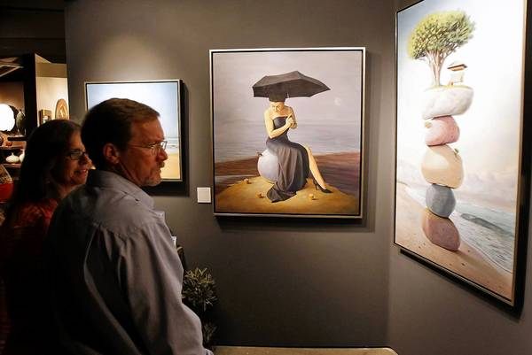 Guests pause to stare at the work of Paul Bond during the Festival of Arts opening night party Saturday.