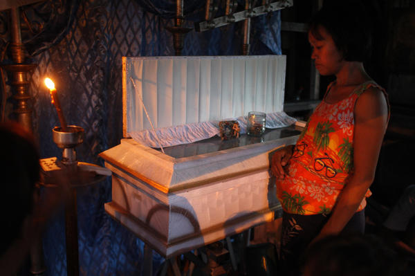 Nelly Ariola, 28, pregnant with her fifth child, looks down at the casket of her son Kelly in Manila. She and her husband walked more than a mile to a government hospital after the infant fell ill, apparently with pneumonia brought on by malnutrition. The couple could not afford transport to the hospital and, after he died, were struggling to come up with the money to bury him.
