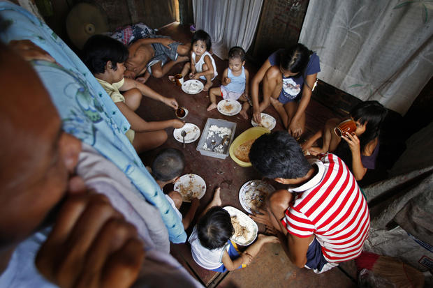 The Naz family gathers for a meal, in the same room where everyone sleeps. When food is especially scarce, only the children eat. About a third of Manila's residents live in poverty. (Rick Loomis / Los Angeles Times)