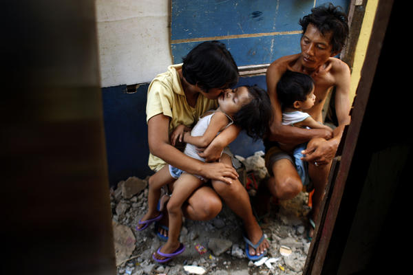Yolanda and Noel sit in the alley outside their shack with two of their children. They scramble each day to get the money to feed the family. Although she is a Roman Catholic, Yolanda disagrees with the church's opposition to contraception and is part of a lawsuit challenging the city ban