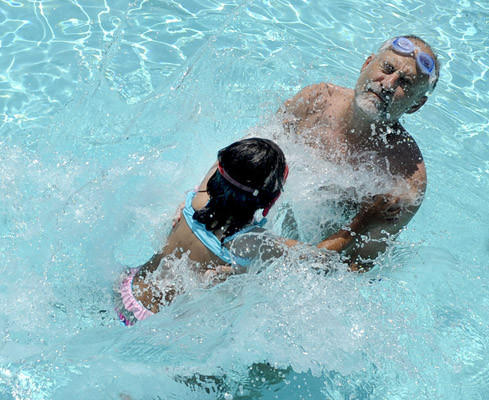 Annalise Ytkin, 5, splashes her father Steve Ytkin as the two Nazareth residents cool off in the Nazareth Park Pool in 90-degree weather Thursday.