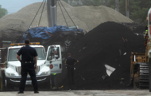 Emergency crews recover a body in the wreckage of a train derailment, Thursday, July 5, 2012. A freight train hauling coal derailed on Union Pacific tracks near Willow Road and Shermer Avenue by the Northbrook-Glenview border on July 4.