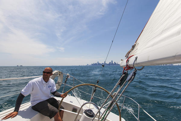 Matt Smart helms a sail boat in Lake Michigan with the Chicago skyline seen in the distance.