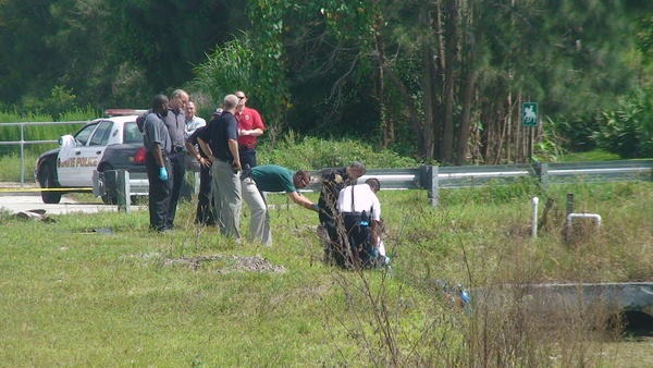 Police help a diver pull the body of a man from a canal in Davie