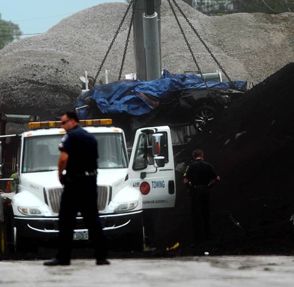 A crane Thursday lifts a nearly flattened car found under tons of coal and debris from Wednesday's railroad bridge collapse over Shermer Road near the border of Glenview and Northbrook. Two bodies were found in the car, authorities said.