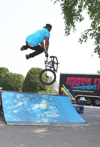 Cartoon Network staffer, Brandon Hopkins of Dallas, Texas, inspires children to exercise as he demonstrates some ambitious tricks on a bike Thursday during the Move It Movement Tour at Boyne Mountain in Boyne Falls.