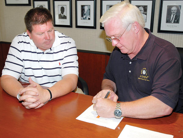"Charlevoix Mayor Norman ""Boogie"" Carlson Jr. (left) watches as Steve Libert of Great Lakes Exploration Group signs an agreement with the State of Michigan and Republic of France in 2010"