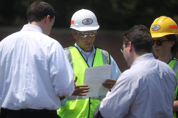 Attorneys Michael LaMonica, left, and Erron Fisher, 2nd from right, present a stop work order to officials on the site of a fatal train derailment and bridge collapse. The train derailment on Wednesday morning caused the collapse of a bridge, killing two people in a car traveling under the bridge.