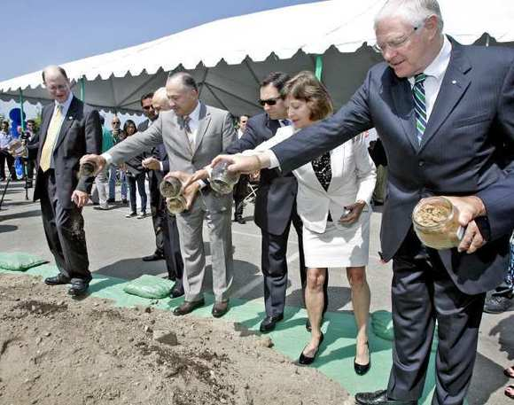 Rep. Brad Sherman stands at left as others, including L.A. County Supervisor Mike Antonovich, right, empty containers of dirt from other transportation centers during a ground breaking for the transit center on Friday, July 6, 2012.