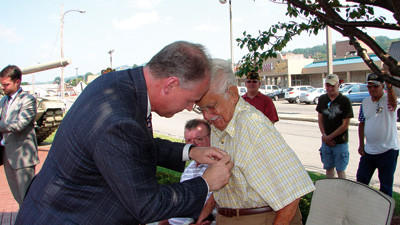 U.S. Rep. Mark Critz, D-Johnstown, pins the first of five decorations on John Merx, Johnstown, who served in the Army during World War II.