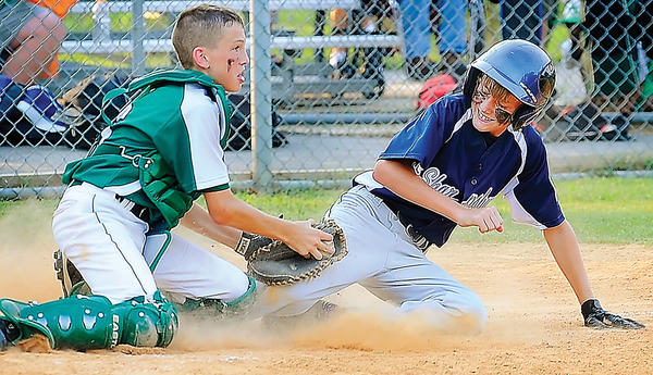 National catcher Dawson Hottinger, left, blocks the plate and takes out Sharpsburg's Kelton Brown for the second out of the fifth inning of National's 2-1 victory on Friday in the Maryland District 1 11-12 tournament.