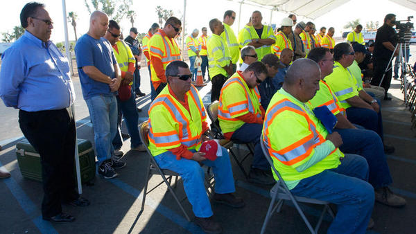 California Department of Transportation workers pray during the Sunbeam rest area dedication Friday in honor of Jaime Obeso.