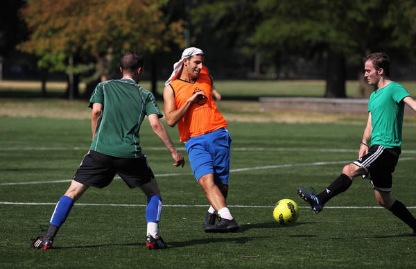 Men play soccer at McKinley Park on Saturday morning during a sunny but cooler day in Chicago.
