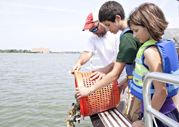 Yancey Powell, educator of Chesapeake Bay Foundation, helps Victor, 13, and Carmen Wharry, 10, of King George County, Virgina, plant oysters into Back River near Langley Air Force Base in Hampton on Saturday.