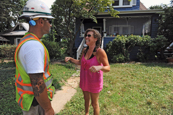 Vanessa Burnham, right, a residents of the 700 block of Hollen Road reacts after hearing from BGE crewman Jesse Palmisano, left, that her home's electrical power might be restored today. The neighborhood has been without electrical power for almost a week since last Friday's storm.