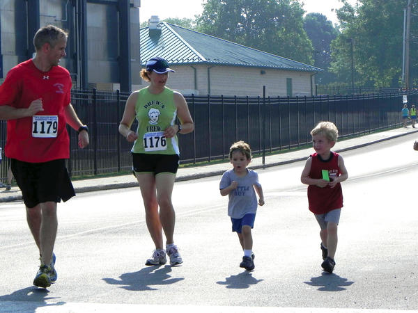 Randy Taylor of Shippensburg, Pa., gives some words of encouragement to Marcie Taylor, their son, Seth, 3, and family friend, Noah Chambers, 4, on Saturday during the one-mile fun run/walk at the Tim and Susan Cook Memorial ChambersFest 1-Mile Race in Chambersburg, Pa.