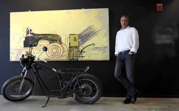 Jim Jacoby, founder and president of Manifest Digital, stands by a motorcycle-inspired art piece at his headquarters in the Jewelers Building in Chicago.